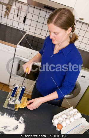 Woman Making Pasta stock photo, A young woman is making pasta on the counter in her apartment kitchen. by Tyler Olson
