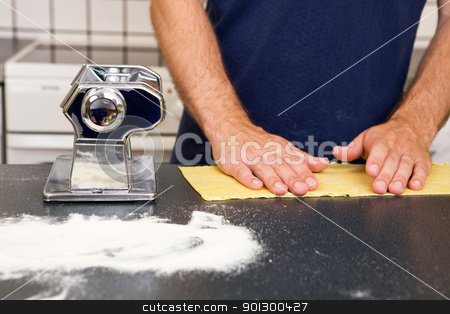 Making Pasta Detail stock photo, A Male making pasta on the counter in the kitchen. by Tyler Olson