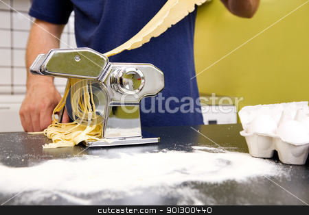 Making Fettuccine stock photo, Fettuccine coming out of a manual pasta machine by Tyler Olson
