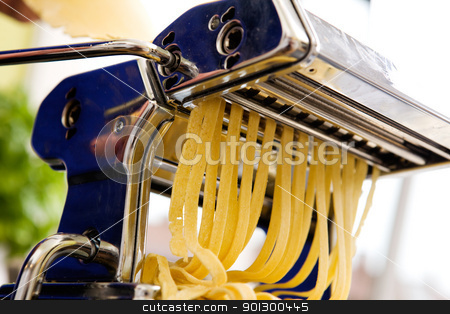 Homemade Pasta Fettuccine Detail stock photo, Fettuccine coming out of a manual pastamachine - shallow depth of field with focus on the pasta by Tyler Olson