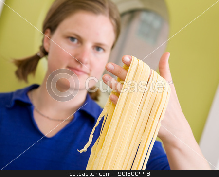 Homemade Pasta Fettuccine Detail stock photo, A proud young woman with fresh homemade fettuccine looks at the camera- shallow depth of field with focus on the pasta by Tyler Olson