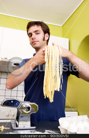 Proud Homemade Fettuccine Chef stock photo, A proud young man with fresh homemade fettuccine looks at the camera- shallow depth of field with focus on the pasta by Tyler Olson