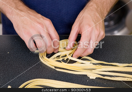 Homemade Fettuccine stock photo, A detail of homemade fettuccine being rolled into a nest by Tyler Olson