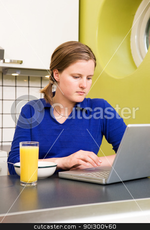 Online Breakfast stock photo, A young woman using the computer at breakfast or eating a meal in the kichen. by Tyler Olson