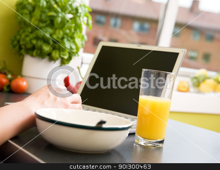 Online Breakfast stock photo, A computer in the kitchen with a bowl of soupr or cereal and orange juice - shallow depth of field with focus on juice and hand by Tyler Olson