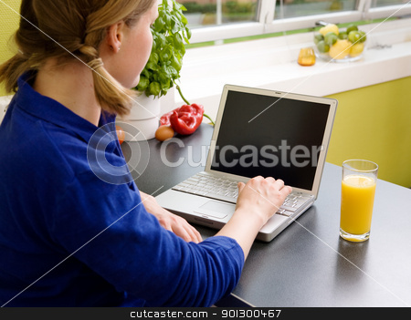 Woman turning on computer stock photo, A young woman turns on the laptop while drinking orange juice by Tyler Olson