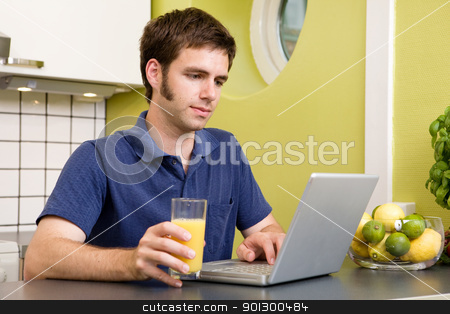 Using Computer with Juice stock photo, A young male works on the computer in the kicthen with a glass of orange juice by Tyler Olson