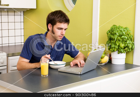 Kitchen Computer Work stock photo, A young male works on the computer in the kicthen while eating breakfast by Tyler Olson