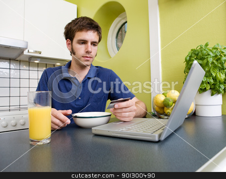 Shopping during Breakfast stock photo, A young male shops online with a credit card in his kitchen while eating breakfast by Tyler Olson