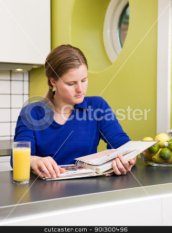 Looking at Recipes stock photo, A young woman in the kitchen looking at recipes. by Tyler Olson