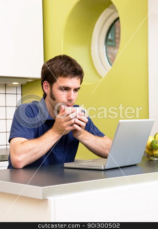 Kitchen Computer stock photo, A young man uses the computer in the kitchen while enjoying a warm drink. by Tyler Olson