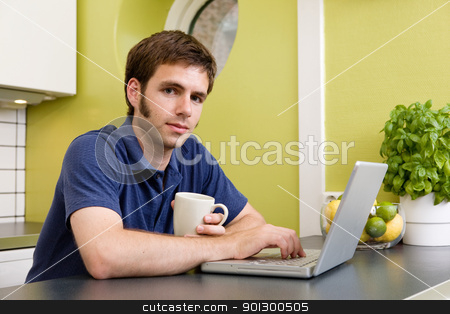 Young Man with Warm Drink at Computer stock photo, A young man uses the computer in the kitchen while enjoying a warm drink by Tyler Olson