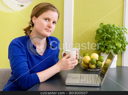 Online in the Morning stock photo, A young woman sitting in the kitchen with a coffee and a computer looking at the camera. by Tyler Olson