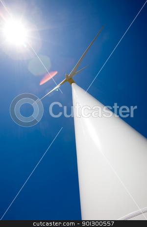 Sun and Wind stock photo, A wind turbine and the sun against a deep blue sky.  Image has heavy lens flare from the sun. by Tyler Olson