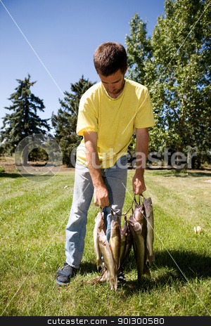 Fresh Catch stock photo, A group of freshly caught fish being held by a male by Tyler Olson