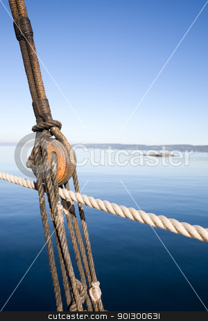 Boat Pulley Abstract stock photo, A boat pulley and rope system against a ocean landscape. by Tyler Olson