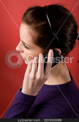 Cell Phone stock photo, A young female listening on a cell phone. isolated on red. by Tyler Olson