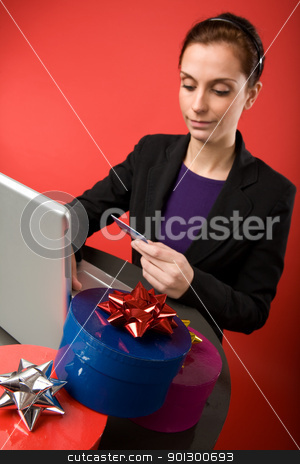 Online Present stock photo, A young female shopping for christmas presents online.  Focus is on the presents with the model and computer blurred. by Tyler Olson