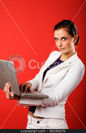 Valentines Email stock photo, A young business woman or student using a laptop with a strong red background by Tyler Olson