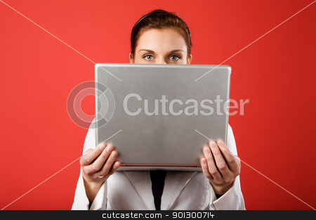 Hidden Identity stock photo, A young woman hiding behind and using a laptop computer wirelessly by Tyler Olson