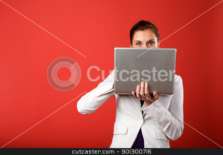 Secret Email stock photo, A young woman hiding behind and using a laptop computer wirelessly by Tyler Olson