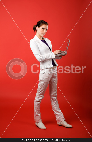 Writing an Email stock photo, A young woman typing on a laptop computer isolated on red by Tyler Olson