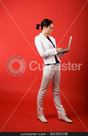 Valentines Email stock photo, A young woman typing on a laptop computer isolated on red by Tyler Olson