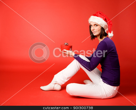 Gift Giving stock photo, A young woman with a present isolated on red by Tyler Olson