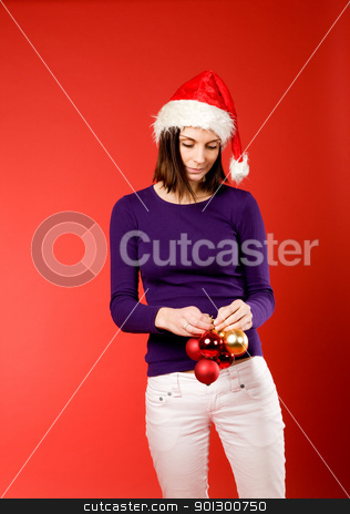 Shy Female with Christmas Decorations stock photo, A young female holding up christmas decorations by Tyler Olson
