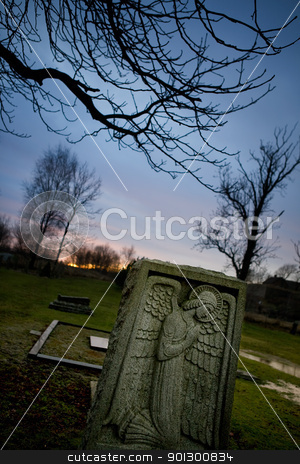 Angel Tombstone stock photo, A spooky graveyard with a deep blue sky and an angel tombstone by Tyler Olson