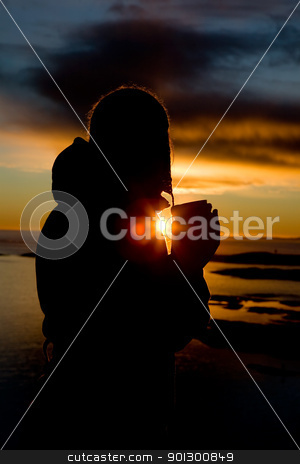 Ocean Silhouette stock photo, A person standing by the Ocean drink a warm drink at sundown by Tyler Olson