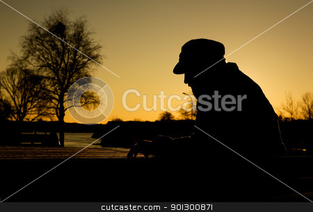 Depressed Man stock photo, A depressed thoughtful man by the water at sundown.  Warm sunlight creating a silhouette. by Tyler Olson