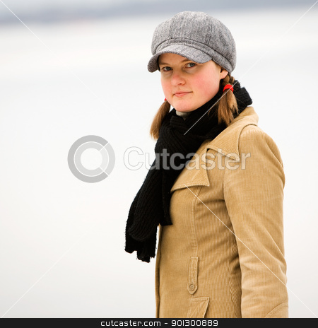 Winter Smile stock photo, A young woman standing by the ocean in winter by Tyler Olson