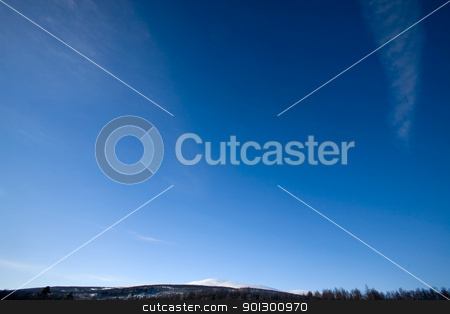 Deep Blue Sky Background stock photo, A deep blue sky background with faint clouds and a sliver of mountains by Tyler Olson