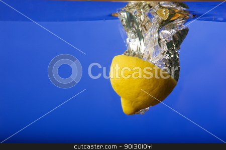 Lemon Falling in Water stock photo, A lemon with a blue background in water by Tyler Olson
