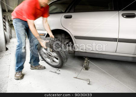 Quick Wheel Change stock photo, A male changing a tire on a car in a garage by Tyler Olson