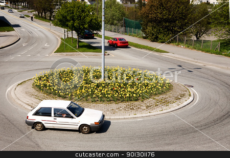 Traffic Circle stock photo, A traffic circle with a white car going around by Tyler Olson