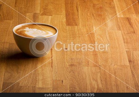 Cappuccino stock photo, A warm specialty coffe on a wood table by Tyler Olson