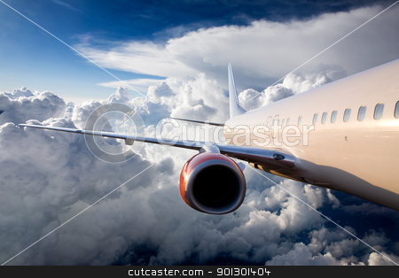 Airplane in Sky stock photo, An airplane flying over a dramatic sky by Tyler Olson