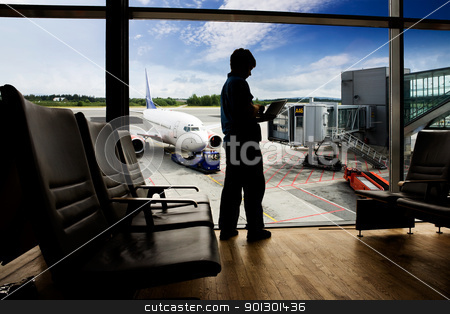 Airport Terminal  Computer  stock photo, A young man using a laptop in an airport terminal by Tyler Olson