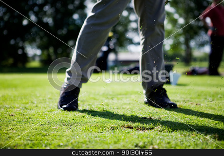Golf Swing stock photo, Golf Swing with grass flying in air.  Focus on the flying grass. by Tyler Olson