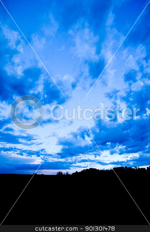 Blue Landscape stock photo, A blue evening sky with clouds on the prairie by Tyler Olson