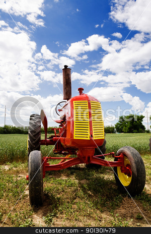 Old Retro Tractor stock photo, An old red retro tractor in a field by Tyler Olson