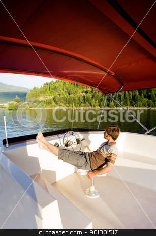 Luxury Boat Owner stock photo, A young male enjoying a luxury boat by Tyler Olson