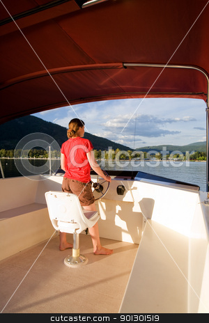 Woman Driving a Yacht stock photo, A young woman driving a yacht from the upper helm by Tyler Olson