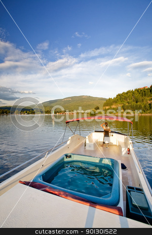 Luxury on a Lake stock photo, A young male at the helm of a luxury boat by Tyler Olson