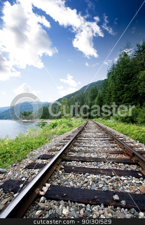Train Tracks stock photo, Train tracks near a large lage going through the mountains by Tyler Olson
