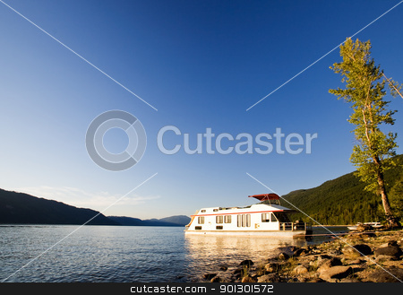Luxury House Boat stock photo, A luxury house boat beached on a beautiful lake by Tyler Olson