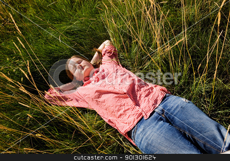 Country Farm Girl stock photo, A country farm girl relaxing in the grass by Tyler Olson
