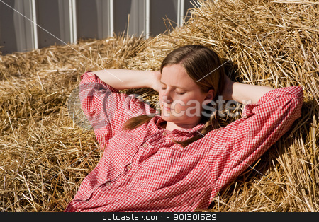 Country Girl stock photo, A country girl laying in a bale of straw by Tyler Olson